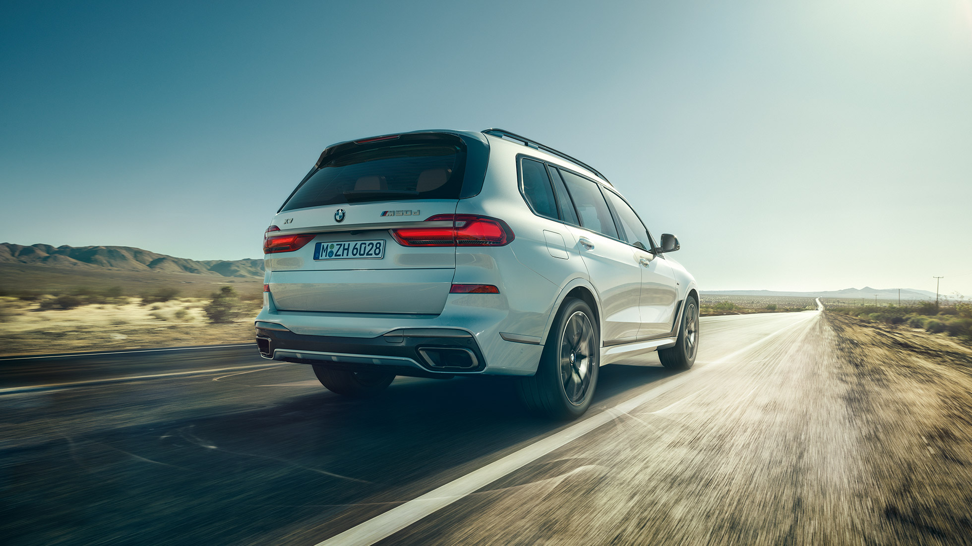 BMW X7 M50i: rear shot of the driving, white BMW X7